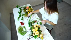 El técnico floral de sexo femenino enganchó a arreglar las flores para el evento en oficina en d3ia almacen de video