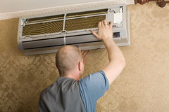 El técnico instala un nuevo acondicionador de aire imagen de archivo