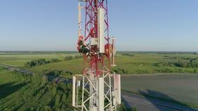 El técnico que trabaja en el trabajo peligroso utiliza el artilugio encima de la antena celular, vuelo del abejón alrededor de la almacen de video
