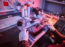 El técnico repara una tableta quebrada en un taller de reparaciones Iluminación con las luces rojas y azules foto de archivo libre de regalías