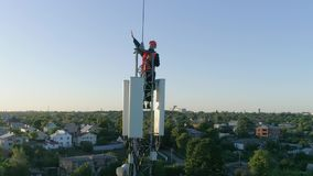 El técnico trabaja encima de la antena celular, muestra el pulgar para arriba y sonríe en el fondo de la puesta del sol almacen de video