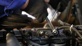 El técnico tuerce los tornillos en el motor del camión en la comprobación del primer almacen de metraje de vídeo