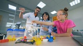 El técnico y los niños masculinos de laboratorio están montando un mecanismo almacen de video