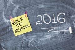 El título de nuevo a escuela en trozo de papel y titula 2016 escrito por la tiza en la pizarra Imagenes de archivo