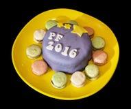 El título PF 2016 escrito en la torta festiva con los macarrones hechos a mano Imagen de archivo libre de regalías