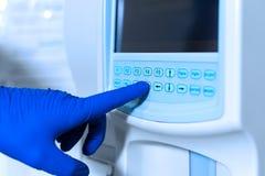 El t?cnico de laboratorio ajusta el dispositivo del an?lisis de sangre m?dico muy exacto foto de archivo