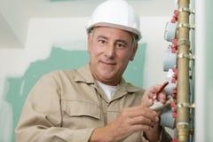 El t?cnico del fontanero trabaja con el contador del agua foto de archivo libre de regalías