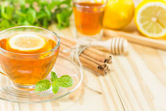 El té con canela y el limón de la miel de la menta en el fondo de madera, t caliente Foto de archivo