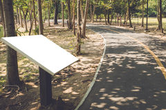 El tablero blanco es lado del camino en parque público Imagen de archivo