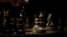 El tablero de ajedrez y el ajedrez, el rey oscuro pone el control almacen de metraje de vídeo