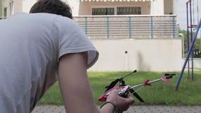 El tablero de chapaleta aplaude y el hombre saca el helicóptero nano de la caja y lo gira almacen de video