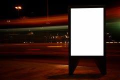 El tablero de la información pública en ciudad de la noche con los coches se enciende en el fondo, haciendo publicidad de mofa en imagenes de archivo
