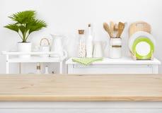 El tablero de la mesa de Brown con el copyspace sobre cocina borrosa deja de lado con los utensilios fotos de archivo