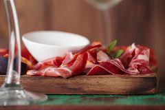 El tablero de madera Assorted curó las carnes, aceite de oliva Fotografía de archivo