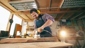 El tablero de madera está consiguiendo pulido por un carpintero de sexo masculino Artesano que trabaja en carpintería metrajes