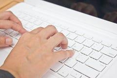 El tablero dominante del ordenador portátil que mecanografía de la mano. imagen de archivo libre de regalías