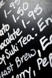 El tablero escrito mano del menú de la tiza ofreció el té de la palabra prominente Fotos de archivo