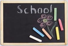 El tablero negro de los niños para dibujar con los creyones coloreados con la escuela de la inscripción imagenes de archivo