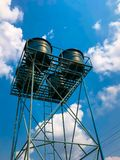 El tanque de agua azul en la torre en el agua fotografía de archivo