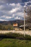 El tanque de agua oxidado viejo delante de casas putrefactas viejas en Georgia foto de archivo libre de regalías