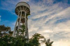 El tanque de agua que ha sido árboles cubiertos en el cielo brillante imagen de archivo