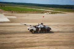 El tanque de los militares o de ejército listo para atacar y moviéndose sobre un terreno abandonado del campo de batalla foto de archivo