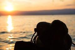 El tanque del buceo con escafandra y aletas y sombrero silueteados del verano en la puesta del sol imagen de archivo libre de regalías