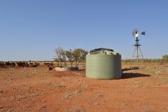 El tanque y molino de viento de agua en australiano interior con ganado y la acción Foto de archivo libre de regalías