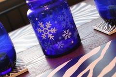 El tarro de cristal azul con los copos de nieve y la cebra blancos raya la decoración Foto de archivo libre de regalías