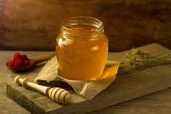 El tarro de cristal de miel con un drizzler, frambuesas, tela del yute, secó las flores en backgroun de madera Fotografía de archivo libre de regalías