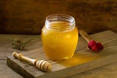 El tarro de cristal de miel con un drizzler, frambuesas, tela del yute, secó las flores en fondo de madera Fotos de archivo libres de regalías