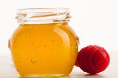 El tarro de cristal llenó de la miel de oro pegajosa dulce y del palillo rojo Fotos de archivo libres de regalías