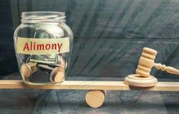 El tarro de cristal y la inscripción 'alimentos 'y el martillo del juez están en las escalas Pago de los alimentos de uno de los  imagen de archivo libre de regalías