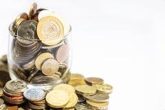 El tarro de dinero, diversa moneda acuña desbordar en el fondo blanco foto de archivo