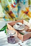 El tarro de granos de café fijó con una taza de café y de accesorios Foto de archivo