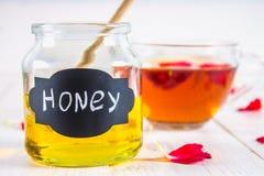 El tarro de la miel etiquetó la miel con una cuchara, en una tabla blanca contra Fotos de archivo libres de regalías