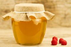 el tarro de miel cerró el paño y las frambuesas del yute en fondo de madera Fotos de archivo libres de regalías