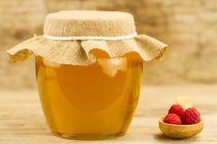 el tarro de miel cerró el paño y las frambuesas del yute en fondo de madera Foto de archivo