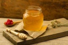 El tarro de miel con el drizzler, frambuesas, tela del yute, secó las flores en fondo de madera Imagen de archivo