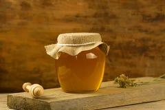 El tarro de miel con el drizzler, tela del yute, secó las flores en fondo de madera Fotografía de archivo libre de regalías