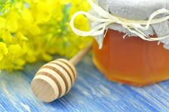 El tarro de miel deliciosa en un tarro con la rabina florece Fotos de archivo