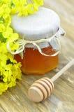 El tarro de miel deliciosa en un tarro con la rabina florece Imagen de archivo