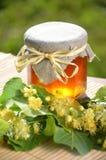 El tarro de miel fresca y deliciosa con el tilo florece Foto de archivo libre de regalías