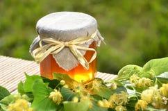 El tarro de miel fresca y deliciosa con el tilo florece Imagen de archivo