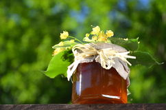 El tarro de miel fresca y deliciosa con el tilo florece Foto de archivo