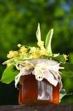 El tarro de miel fresca y deliciosa con el tilo florece Fotos de archivo