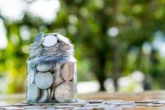 El tarro del dinero llenó de las monedas en bokeh verde Imagenes de archivo