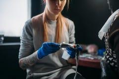 El tattooist de sexo femenino prepara la máquina del tatuaje imagen de archivo