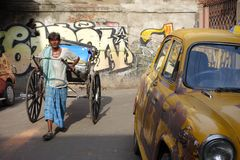 El taxi amarillo icónico Kolkata del embajador y una mano tiraron del carrito Imágenes de archivo libres de regalías