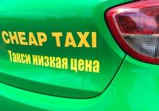 El taxi barato firma en inglés y ruso Imágenes de archivo libres de regalías